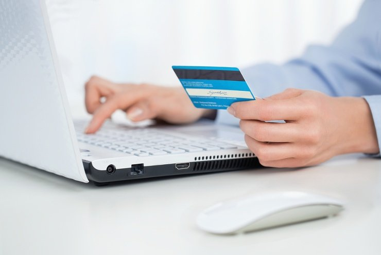 a close up shot of a person sitting at a laptop with a credit card in hand, entering details into the laptop