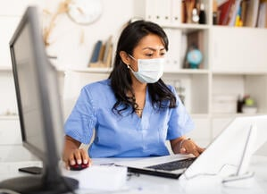 Masked nurse working at a computer